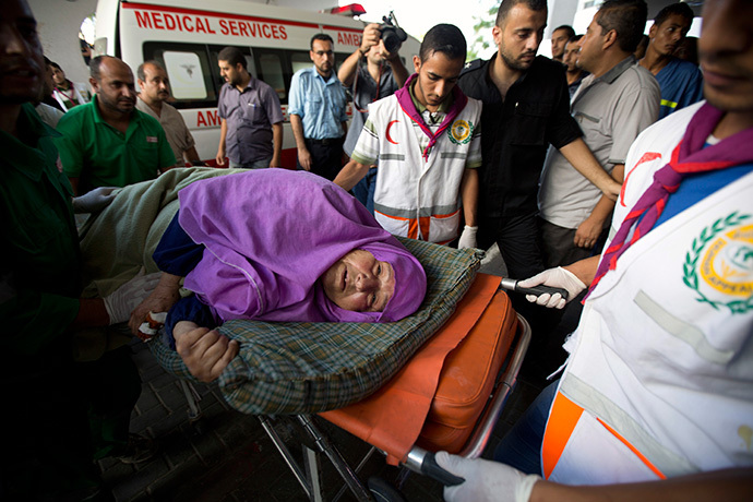 A Palestinian woman is brought into an hospital on a stretcher after she was injured in an Israeli air strike on July 11, 2014 in Gaza City. (AFP Photo / Mohammed Abed)