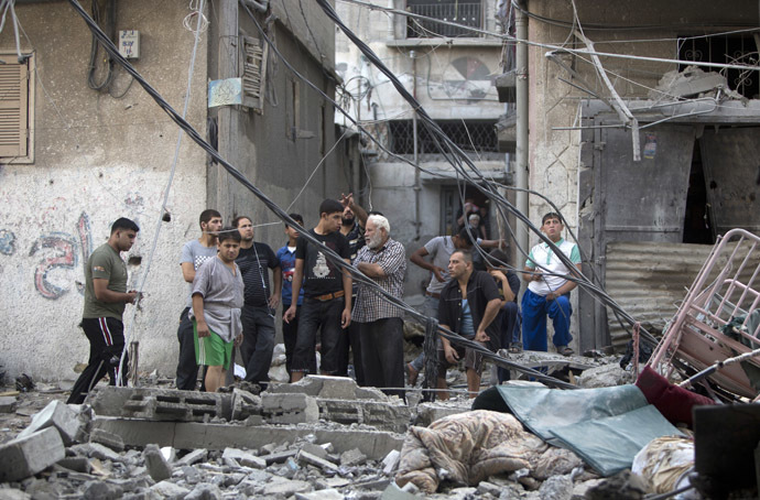 Palestinian men inspect the destruction following an Israeli military strike in Gaza City on July 12, 2014. (AFP Photo)