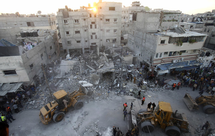 Bulldozers remove debris as Palestinians and rescue workers search for victims under the rubble of a house which police said was destroyed in an Israeli air strike in Rafah in the southern Gaza Strip July 11, 2014. (Reuters/Ibraheem Abu Mustafa)