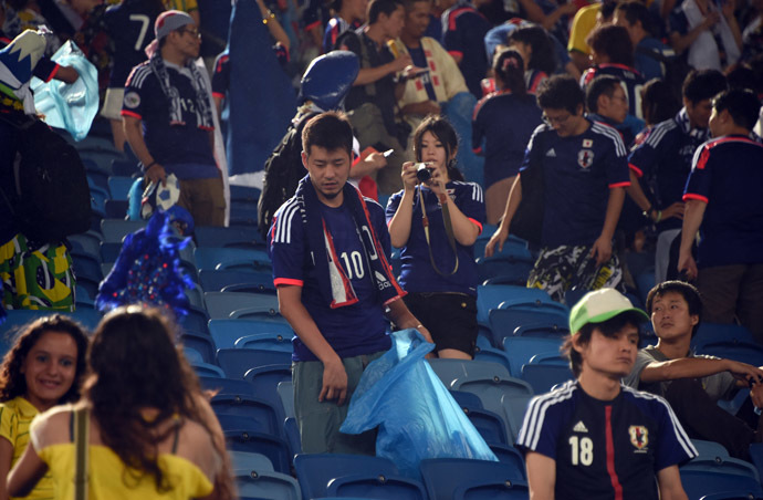 Japanese fan clean the tribune after a Group C football match between Japan and Greece at the Dunas Arena in Natal during the 2014 FIFA World Cup on June 19, 2014. (AFP Photo/Toshifumi Kitamura)