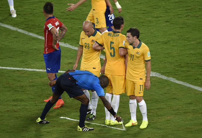 Ivorian referee Noumandiez Desire Doue uses his freekick spray marker during a Group B football match between Chile and Australia at the Pantanal Arena in Cuiaba during the 2014 FIFA World Cup on June 13, 2014. (AFP Photo/Juan Barreto)