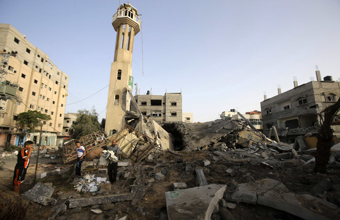 Palestinians survey the rubble of a mosque, which police said was destroyed in an Israeli air strike, in Nuseirat in the central Gaza Strip July 12, 2014. (Reuters/Ibraheem Abu Mustafa)