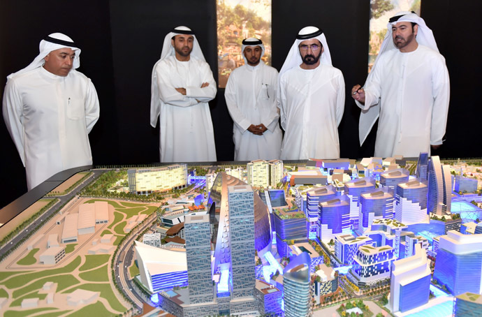 """A handout picture made available on July 6, 2014 by the press office of Sheikh Mohammed Bin Rashid al-Maktoum, ruler of Dubai, shows him (2ndR) looking at the mock-up of the """"Mall of the World"""" project during its presentation in Dubai. (AFP Photo/Sheikh Mohammed Bin Rashid)"""