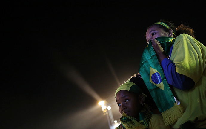 A Brazilian fan and her mother react as they watch a broadcast of the 2014 World Cup third-place playoff between Brazil and the Netherlands on Copacabana beach in Rio De Janeiro, July 12, 2014. (Reuters / Nacho Doce)