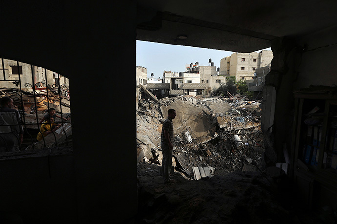 Palestinians survey the rubble of a house which police said was destroyed in an Israeli air strike in the northern Gaza Strip July 12, 2014. (Reuters / Mohammed Salem)