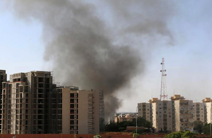 Smoke rises near buildings after heavy fighting between rival militias broke out near the airport in Tripoli July 13, 2014. (Reuters)