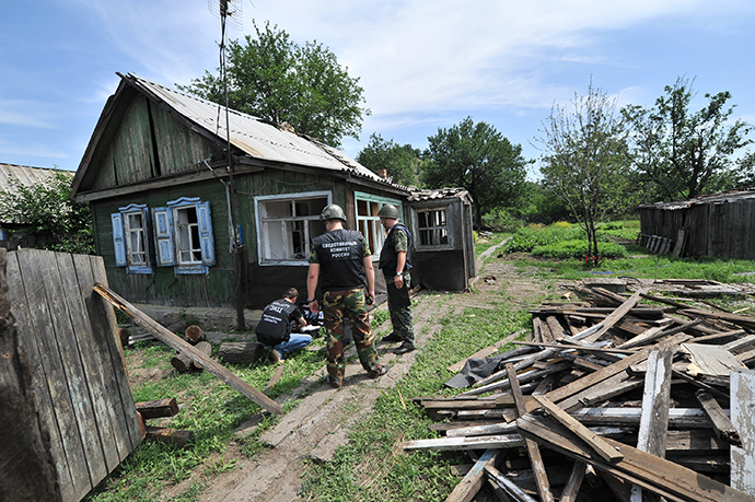 Law enforcement officers work at the area in the town of Donetsk in Russia's Rostov Region which was hit by a high-explosive shell fired from the Ukrainian territory, July 13, 2014. (RIA Novosti / Sergey Pivovarov)