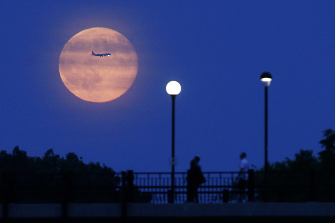 Aircraft passes in front of a Supermoon rising over the Rideau Canal in Ottawa July 12, 2014. (Reuters/Blair Gable)