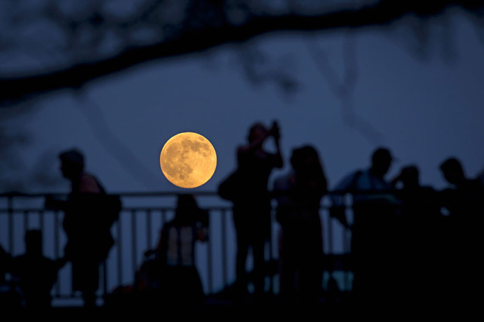 People stand and look at the moon one day ahead of the Supermoon phenomenon from a bridge over 42nd St. in the Manhattan borough of New York July 11, 2014 (Reuters/Carlo Allegri)
