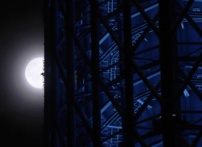 A super moon is seen next to Tokyo Sky Tree, the world's tallest broadcasting tower at 634 metres, in Tokyo July 12, 2014. (Reuters/Yuya Shino)