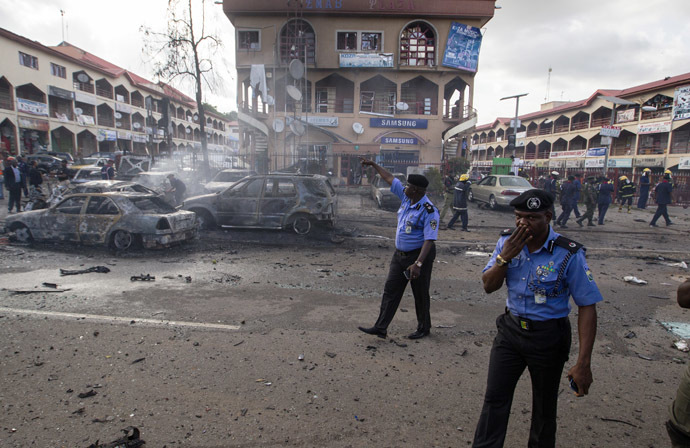 Policemen walk towards burnt vehicles at the scene of a blast at a business district in Abuja June 25, 2014. (Reuters/Afolabi Sotunde)