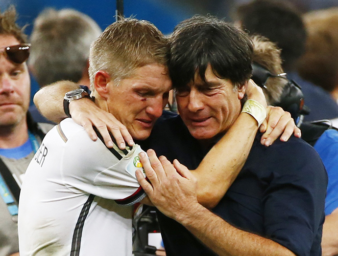 Germany's Bastian Schweinsteiger (L) embraces coach Joachim Loew as they celebrate their win against Argentina after their 2014 World Cup final at the Maracana stadium in Rio de Janeiro July 13, 2014. (Reuters / Michael Dalder)