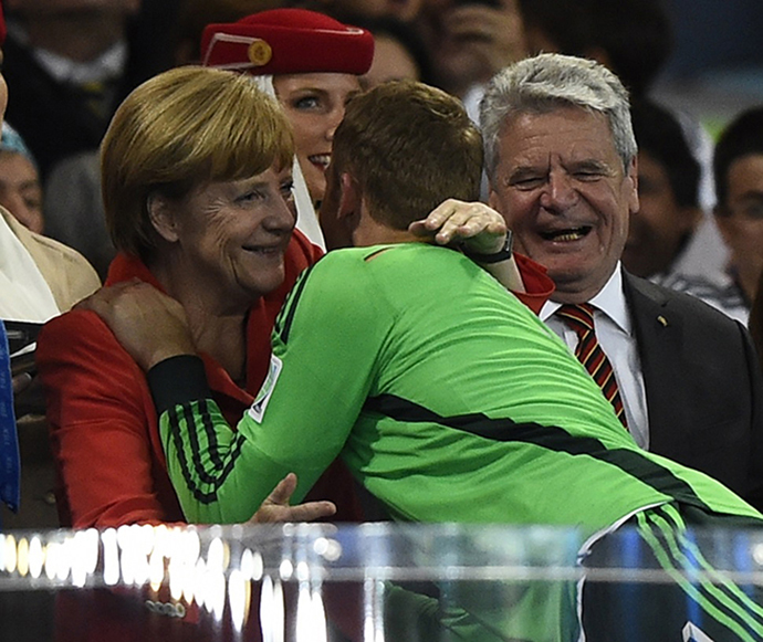 Germany's goalkeeper Manuel Neuer receives a hug from Chancellor Angela Merkel beside President Joachim Gauck (R) after the 2014 World Cup final between Germany and Argentina at the Maracana stadium in Rio de Janeiro July 13, 2014. (Reuters / Dylan Martinez)