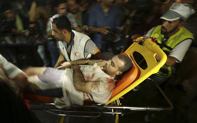A wounded Palestinian, who hospital officials said was injured in an Israeli air strike, is wheeled into a hospital in Gaza City July 12, 2014. (Reuters / Mohammed Salem)