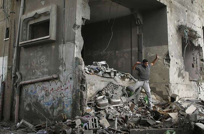 A Palestinian walks amidst the debris of a neighbouring house which police said was damaged after an Israeli air strike destroyed Tayseer Al-Batsh's family house, in Gaza City July 13, 2014. (Reuters / Mohammed Salem)