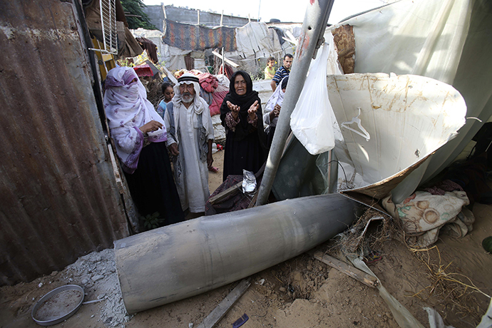 A Palestinian woman gestures as she stands behind a missile which witnesses said was fired by Israeli aircraft, at a shack belonging to Bedouins in Rafah, in the southern Gaza Strip July 13, 2014. (Reuters / Ibraheem Abu Mustafa)