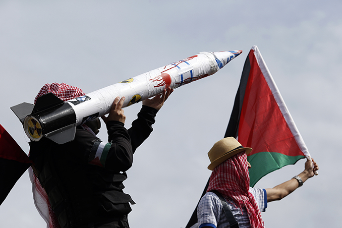 Protesters wearing kaffiyehs hold a Palestinian flag and a fake rocket with the Israeli flag, swastikas and a nuclear symbol on July 13, 2014 in Paris, during a demonstration against Israel and in support of residents in the Gaza Strip. (AFP Photo / Kenzo Tribouillard)