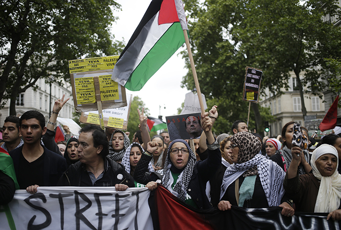 "Protesters hold Palestinian flags banners and placards, including one with the image of French president Francois Hollande and the word ""assassin"", on July 13, 2014 in Paris. (AFP Photo / Kenzo Tribouillard)"