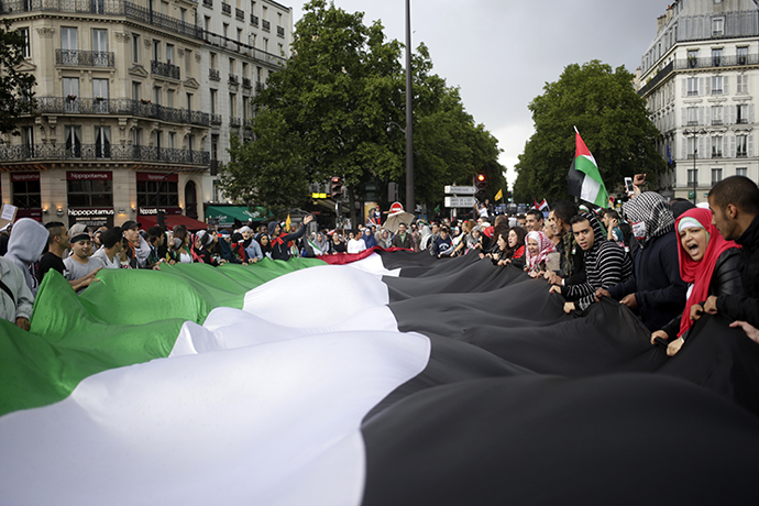 Protesters hold a large Palestinian flag on July 13, 2014 in Paris, during a demonstration against Israel and in support of residents in the Gaza Strip. (AFP Photo / Kenzo Tribouillard)