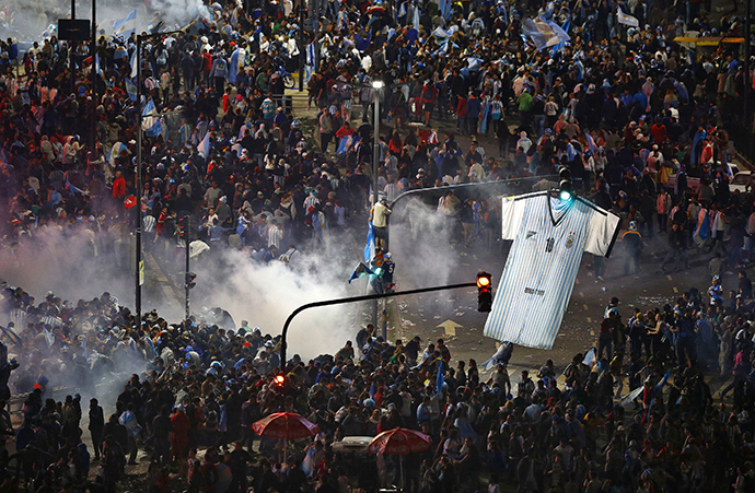 Argentina's fans run away from tear gas as they clash with riot police in Buenos Aires after Argentina lost to Germany in their 2014 World Cup final soccer match in Brazil, July 13, 2014. (Reuters / Ivan Alvarado)