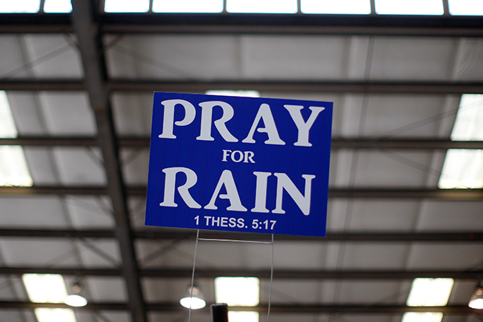 A sign advising to pray for rain hangs above an exhibit area at the 47th Annual World Ag Expo in Tulare, California (Reuters / David McNew)