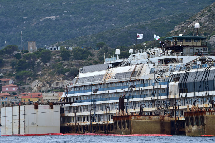 A picture shows the wreck of the Costa Concordia cruise ship starting being lifted out of water during an operation to refloat the boat on July 14, 2014 off the Giglio Island. (AFP Photo / Giuseppe Cacace)