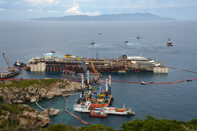 A general view shows the wreck of the Costa Concordia cruise ship and tug boats during an operation to refloat the boat on July 14, 2014 off the Giglio Island. (AFP Photo / Vincenzo Pinto)