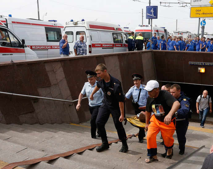 Members of the emergency services carry an injured passenger outside a metro station following an accident on the subway in Moscow July 15, 2014. (Reuters / Sergei Karpukhin)