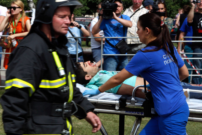 Members of the emergency services attend to an injured passenger outside a metro station following an accident on the subway in Moscow July 15, 2014. (Reuters / Sergei Karpukhin)