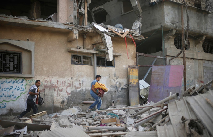 Palestinians carry their belongings as they walk amongst the debris of a house which police said was hit by an Israeli air strike in Gaza City July 15, 2014. (Reuters / Mohammed Salem)