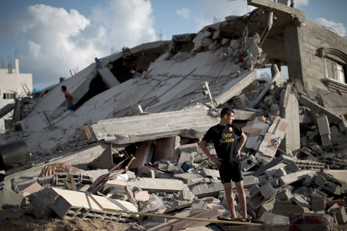 A Palestinian man stands on the rubble of a destroyed building following an Israeli military strike on Beit Lahya, in the northern Gaza Strip on July 15, 2014. (AFP Photo / Mahmud Hams)