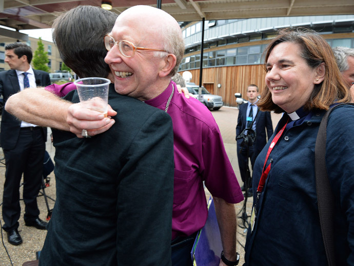 Bishop of Oxford John Pritchard (C) hugs a female member of the clergy after the Synod session which approved the consecration of women bishops, in York July 14, 2014. (Reuters / Nigel Roddis)
