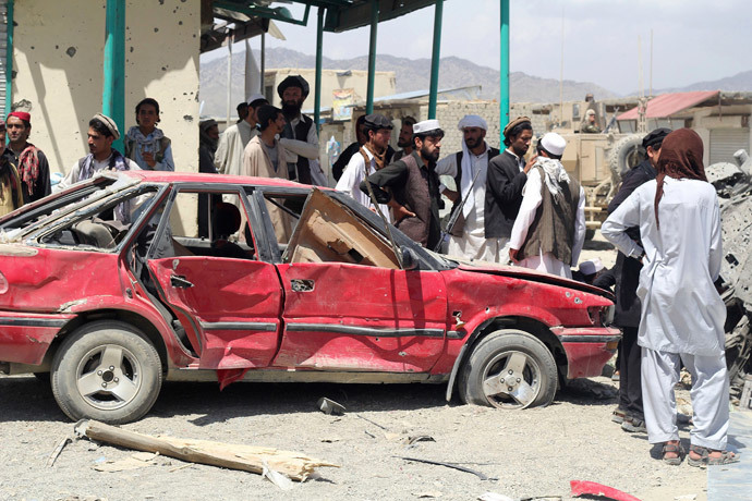 Villagers gather at the site of a car bomb attack in Urgon district, eastern province of Paktika July 15, 2014. (Reuters / Stringer)