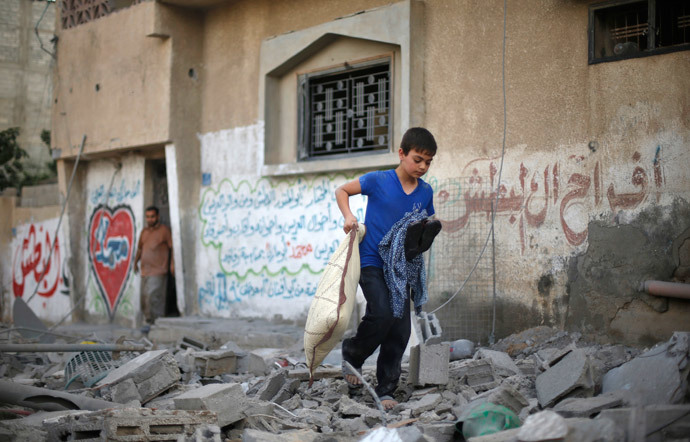 A Palestinian boy carries his belongings as he walks amongst the debris of a house which police said was hit by an Israeli air strike in Gaza City July 15, 2014. (Reuters / Mohammed Salem)