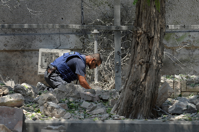 An Israeli bomb disposal expert inspects the remains of a rocket fired by Palestinian militants from the Gaza Strip that hit a yard outside a house in the southern port city of Ashdod on July 15, 2014 (AFP Photo / David Buimovich)