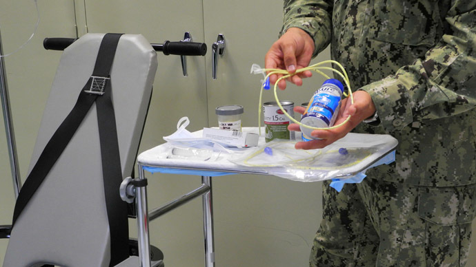 A US naval medic holds liquid food supplement force fed to hunger strikers at the US Naval Base in Guantanamo Bay, Cuba (AFP Photo / Chantal Valery)