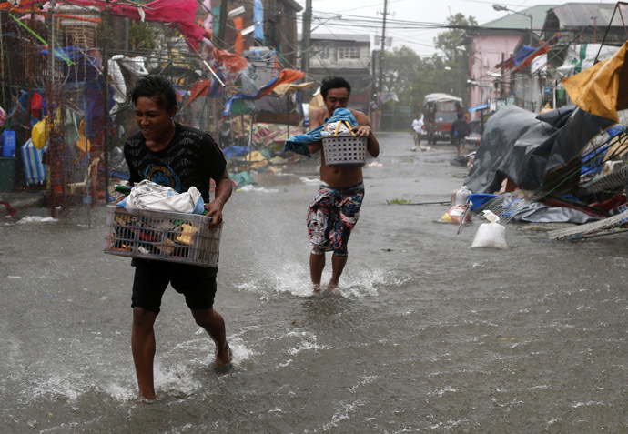 Residents carry their belongings as Typhoon Rammasun (locally named Glenda) hit the town of Imus, Cavite southwest of Manila, July 16, 2014. (Reuters)