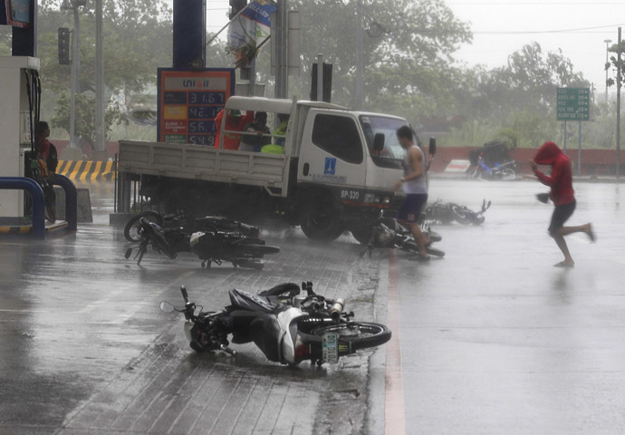 People run towards a gas station to take cover past fallen motorcycles on a main road after strong winds brought by Typhoon Rammasun, locally called Glenda, battered the capital, metro Manila July 16, 2014. (Reuters)