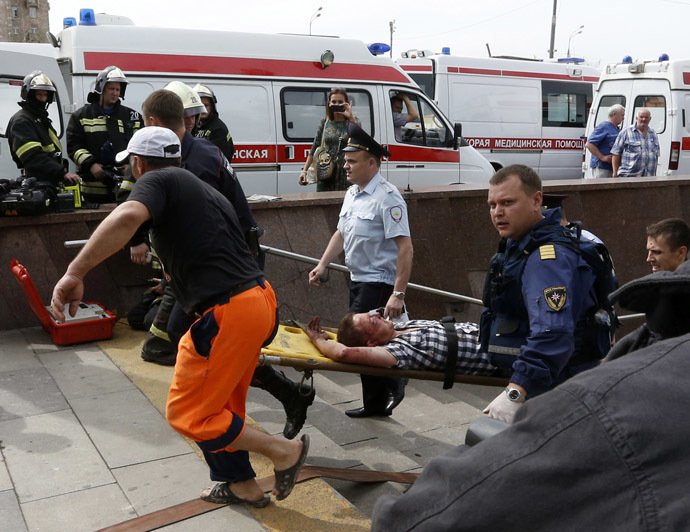 Members of the emergency services carry an injured passenger outside a metro station following an accident on the subway in Moscow July 15, 2014. (Reuters/Sergei Karpukhin)