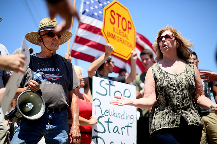 Immigrant rights activist Mary Estrada (R) speaks with anti-immigration activists during a protest outside of the U.S. Border Patrol Murrieta Station on July 7, 2014 in Murrieta, California. (AFP Photo / Getty Images / Sandy Huffaker)