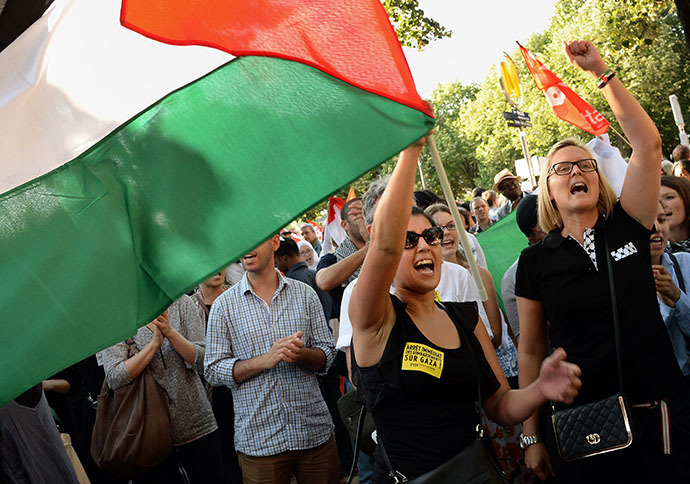 A woman holds a Palestinian flag as she protests on July 16, 2014 with others on the central Invalides square in Paris against Israel's deadly bombing of Gaza. (AFP Photo / Pierre Andrieu)