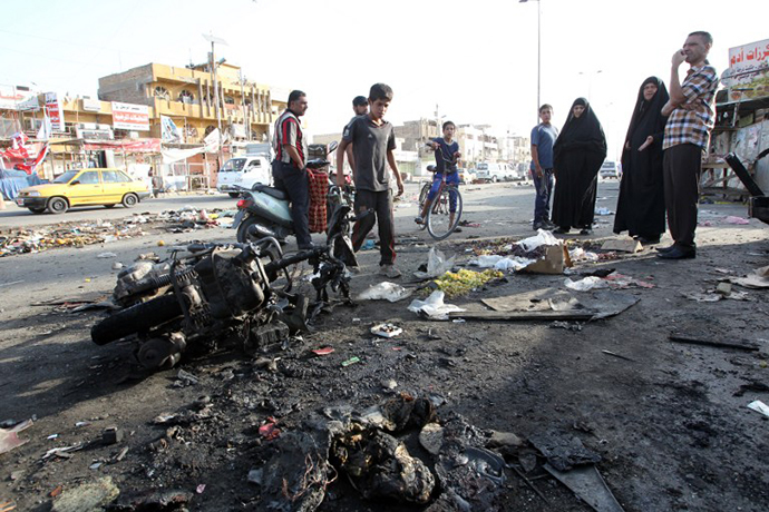 Iraqi onlookers gather on July 16, 2014 around a burnt motorcycle at the scene of an explosion that took place the previous night in Sadr City, one of Baghdad's northern Shiite-majority districts. (AFP Photo / Ali al-Saadi)