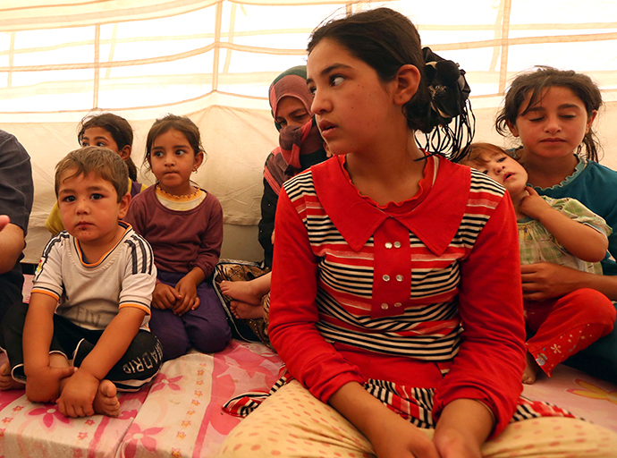 Young displaced Iraqis at the Khazer camp for Iraqi family fleeing violence following last month's jihadist-led offensive on July 17, 2014, at the Kurdish checkpoint in Aski kalak, 40 km West of Arbil, the capital of the autonomous Kurdish region of northern Iraq. (AFP Photo / Safin Hamed)