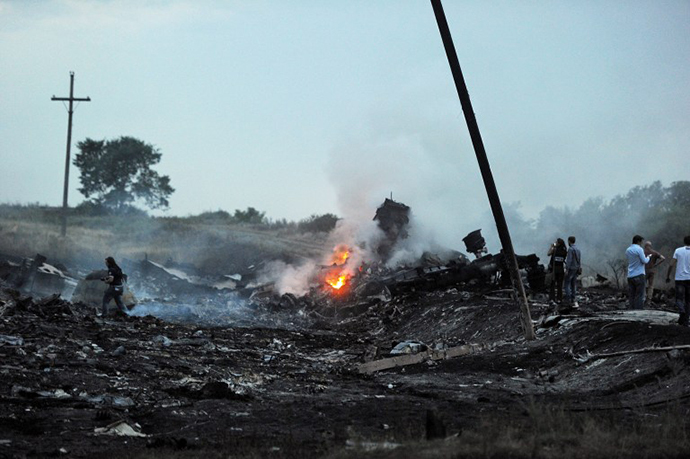 People stand, on July 17, 2014, amongst the wreckages of the malaysian airliner carrying 295 people from Amsterdam to Kuala Lumpur after it crashed, near the town of Shaktarsk. (AFP Photo / Dominique Faget)