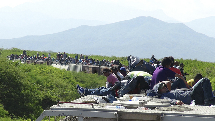 People hoping to reach the U.S. ride atop the wagon of a freight train, known as La Bestia (The Beast) in Ixtepec (Reuters / Jose de Jesus Cortes)