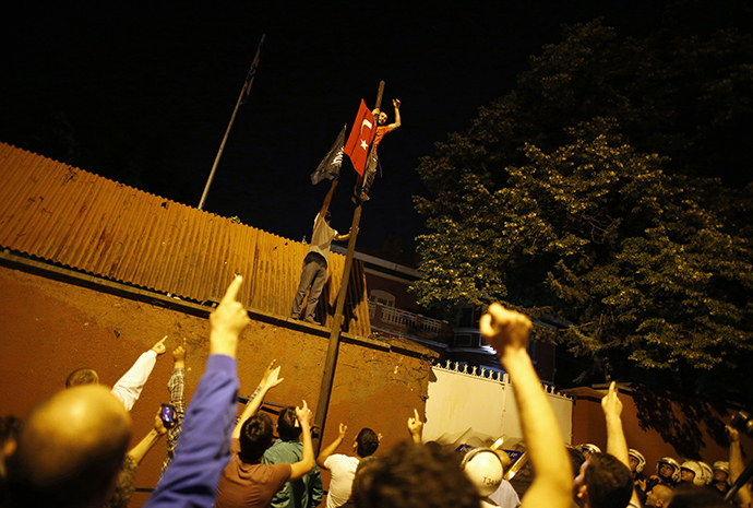 Demonstrators climb a wall and pole at the Israeli Embassy in Ankara as others shout slogans, during a protest against Israel's military action in Gaza, July 18, 2014. (Reuters / Umit Bektas)