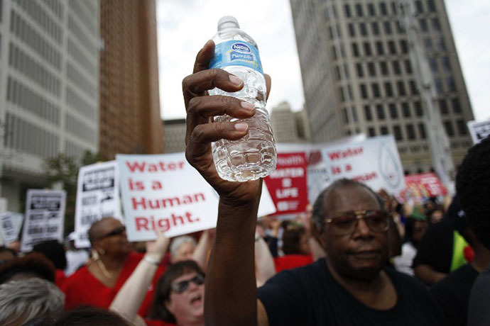 A man holds a bottle of water as he joins other demonstrators protesting against the Detroit Water and Sewer Department July 18, 2014 in Detroit, Michigan. (AFP Photo / Joshua Lott)