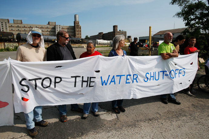Protestors hold a banner across a drive way to block trucks from coming out of the gate of a private-contractor company hired to shut off the water to residential customers with unpaid bills in Detroit, Michigan July 18, 2014. (Reuters / Rebecca Cook)