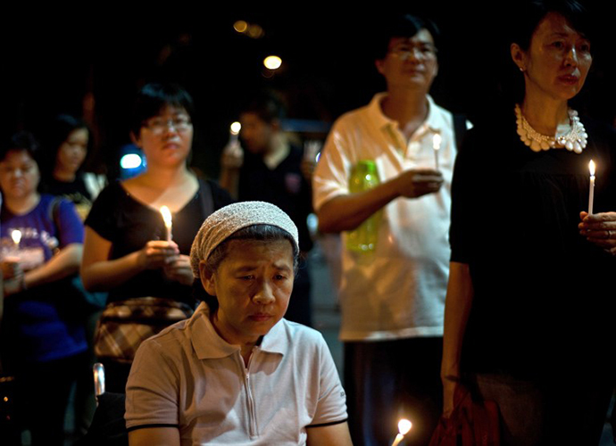 People gather during a candle-light vigil for the victims of the Malaysia Airlines flight MH17, in Kuala Lumpur on July 19, 2014. (AFP Photo / Manan Vatsyayana)