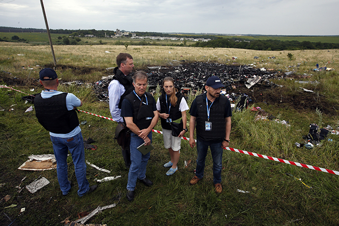 Organisation for Security and Cooperation in Europe (OSCE) monitors stand at the site of Thursday's Malaysia Airlines Boeing 777 plane crash near the settlement of Grabovo in the Donetsk region July 18, 2014. (Reuters / Maxim Zmeyev)
